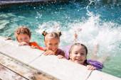 Fotografie aufgeregte Freunde blicken in die Kamera, während Wasser mit Beinen im Pool plätschert