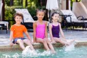 Freunde in Badebekleidung schauen in die Kamera, während sie auf dem Pooldeck sitzen und Wasser mit den Beinen spritzen lassen