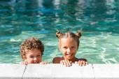 Mädchen blickt in Kamera, während sie Zeit im Schwimmbad mit lockigem Jungen verbringt