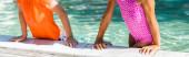 Ausgeschnittene Ansicht von Mädchen im Badeanzug und Jungen im T-Shirt, die sich am Pool lehnen, Panoramaaufnahme