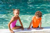 Mädchen im Badeanzug blickt in die Kamera, während sie am Pool neben lockigem Jungen im T-Shirt sitzt