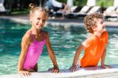 Fotografie Mädchen im Badeanzug lehnt am Pool neben lockigem Jungen im T-Shirt