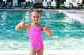dívka v plavkách a slunečních brýlích ukazující palce nahoru, zatímco stojí u bazénu