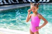lány fürdőruhában megérinti napszemüveg, miközben álló kézzel csípő közelében medence