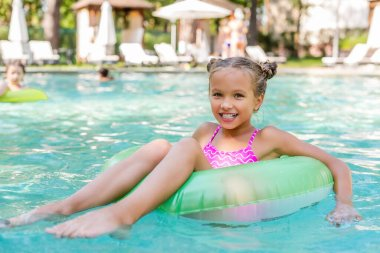 Child looking at camera while floating in pool on inflatable ring stock vector