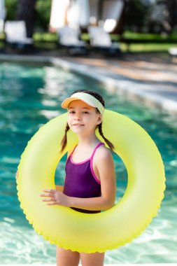 Child in sun visor cap and swimsuit posing with inflatable ring near pool stock vector