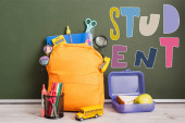 yellow backpack full of school supplies near lunch box, toy school bus and pen holder on desk near green chalkboard with student lettering