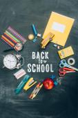 top view váz vintage ébresztőórával, zöld alma és iskolai kellékek fekete táblán vissza az iskolai felirattal