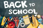 felső nézet érett alma, számológép és iskolai kellékek fekete táblán vissza az iskolai betű