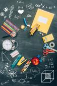 horní pohled na rám s ročníkovými budíky, zeleným jablkem a školními potřebami na černé tabuli s ilustrací