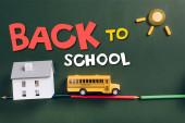 pohled shora na školní autobus na silnici z barevných tužek, model domu a slunce na zelené tabuli s nápisy zpět do školy
