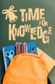 Gelber Rucksack mit Notizbüchern, Scheren, Pinseln und Farbstiften auf grüner Tafel mit Zeit für Wissensschriftzüge