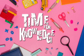 Photo top view of stationery and toy school bus near time for knowledge lettering on pink