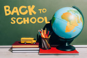 globe and pen holder on notebook near toy school bus on books near green chalkboard with back to school lettering