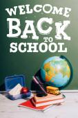 zeměkoule v blízkosti hračky školní autobus a pero držák na knihy v blízkosti oběda box a zelená tabule s zpět do školy nápisy