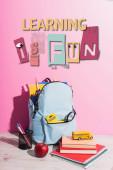 školní batoh plný dopisního papíru, pera držák, zralé jablko, knihy a hračky školní autobus poblíž učení je zábava nápis na růžové