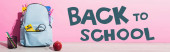 horizontal image of blue backpack with school supplies near whole apple, pen holder with felt pens and back to school lettering on pink