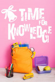 yellow backpack with school supplies, lunch box, toy school bus and pen holder with felt pens near time for knowledge lettering on pink