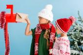 Mädchen im Winteroutfit steckt Umschlag in Briefkasten bei Bruder isoliert auf blau