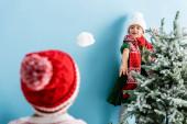 selektivní zaměření dívky v klobouku a šála házení sněhové koule v blízkosti bratra na modré