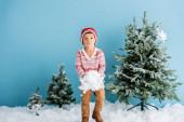Junge im Winteroutfit hält weißen Schnee neben Weihnachtsbäumen auf blauem Grund