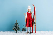 Photo kid in winter outfit standing on snow with ski poles and skis on blue