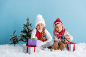 children in winter outfit sitting on snow near presents and firs isolated on blue