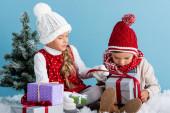 děti v zimním oblečení sedí na sněhu v blízkosti jedlí a drží dárky izolované na modré
