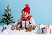 boy in hat and winter outfit sitting near presents and christmas tree while touching snow isolated on blue
