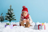 boy in hat and winter outfit sitting on snow and holding present near christmas trees isolated on blue