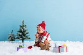 Photo boy in hat and winter outfit sitting on snow and holding present while blowing on hand isolated on blue