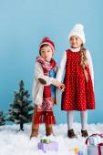 Junge mit Strickmütze hält Händchen mit Schwester in der Nähe von Geschenken auf Schnee isoliert auf blau