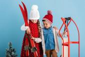 dívka v zimě oblečení drží lyže v blízkosti bratra s sleight na modré