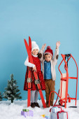 girl in winter outfit holding skis near brother with hands above head standing near sleight and presents on snow isolated on blue