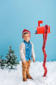 Fotografie boy in hat and winter outfit standing near red mailbox with present on blue