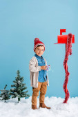 Fotografie boy in winter outfit holding present near red mailbox while standing on blue