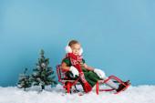 dívka v zimě sluchátka a šála sedí v saních na sněhu v blízkosti borovic na modré