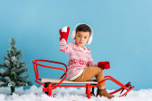 Photo boy in winter earmuffs and sweater sitting in sleigh and holding snowball on blue