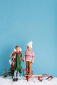 dívka v zimě náušnice a šála stojící s bruslemi a držící se za ruce s bratrem v klobouku u sáně na modré
