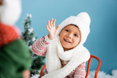 selective focus of boy in knitted scarf and hat waving hand on blue