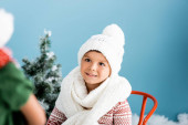 Photo selective focus of boy in knitted scarf and hat on blue