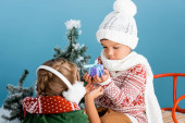 selective focus of boy in knitted hat holding present while sitting on sleight near girl in winter earmuffs on blue