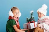 selektivní zaměření dívky v zimě chrániče sluchu v blízkosti chlapce v pleteném klobouku drží dárek na modré