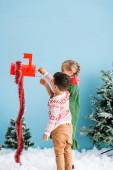 děti dosahují obálky v červené poštovní schránce s dekorací v blízkosti borovic na modré