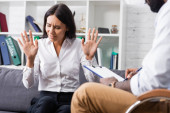 selective focus of frustrated woman gesturing with closed eyes near african american psychologist writing diagnosis on clipboard