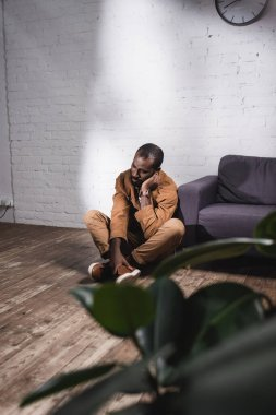 Selective focus of african american man sitting on floor and touching face