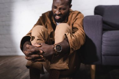 Selective focus of african american man sitting on floor with clenched hands