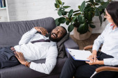 joyful african american man talking to psychologist while lying on sofa