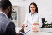 barna orvos megérinti malacka bank, csomagolva kötszer, és így toll afro-amerikai beteg közel biztosítási űrlap