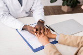 Teilansicht eines afrikanisch-amerikanischen Arztes, der die Hände eines Patienten in der Nähe von Versicherungsantragsformular und Laptop berührt